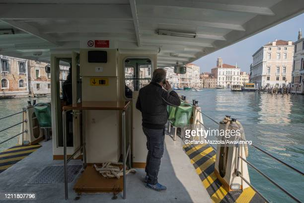 The Vaporini travel around the city with very few people on March 11 2020 A local walks near the Grand Canal with a protective face mask in Venice...