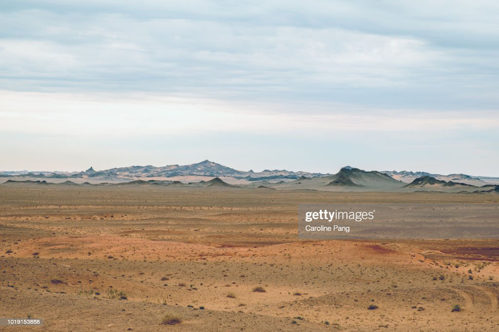 The varied landscape of the Gobi desert includes jagged hills partially covered with sands which create fascinating layers of colours. : Foto de stock