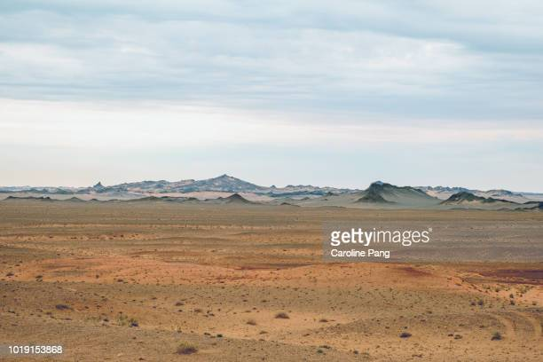 the varied landscape of the gobi desert includes jagged hills partially covered with sands which create fascinating layers of colours. - extreme terrain stock pictures, royalty-free photos & images