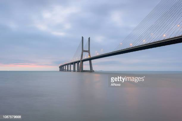 the vasco da gama bridge is a beautiful landmark, and one of the longest bridges in the world. lisbon, portugal in a dawn light. - man made structure stock pictures, royalty-free photos & images