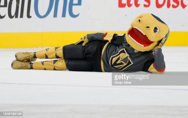 The Vegas Golden Knights mascot Chance the Golden Gila Monster lies on the ice between periods of a game between the Golden Knights and the Edmonton...