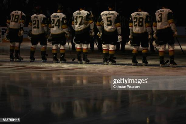 The Vegas Golden Knights stand attended in a moment of silence to honor the victims of the Las Vegas shootings before the NHL game against the...