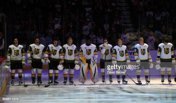 The Vegas Golden Knights stand during in a moment of silence to honor the victims of the Las Vegas shootings before their game against the Arizona...