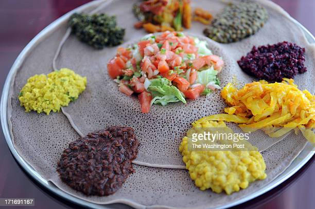 The vegetable combination platter which is served at Lucy contains injera bread on which the vegetables like split peas lentils and cabbage are places