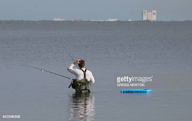 The Vehicle Assembly Building at Kennedy Space Center looms in the distance as a fisherman gets an early start near Port Canaveral Florida on...