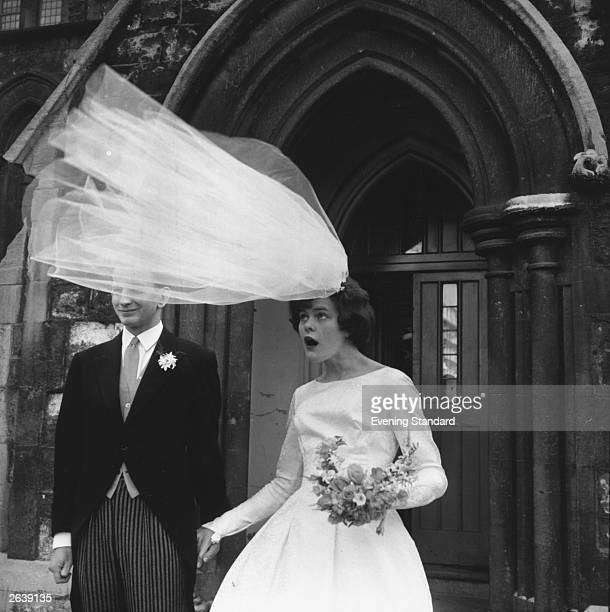 The veil of newlywed bride Eileen Petticrew flies up in a gust of wind as she poses for photographs with husband Robert Greenhill outside St John the...