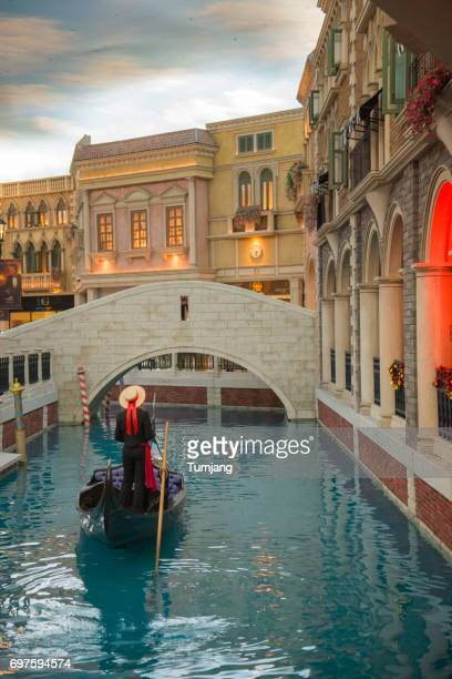the venetian macau resort hotel vertical interior view. gondolier rides tourists on a gondola along the mock venetian canal - the venetian macao stock photos and pictures
