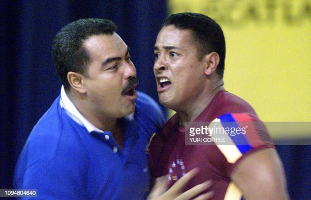 The Venezuela Eudys Gumarra is congratulated by his coach after competing in the weightlifting competition of the 85kg category during the XIX...