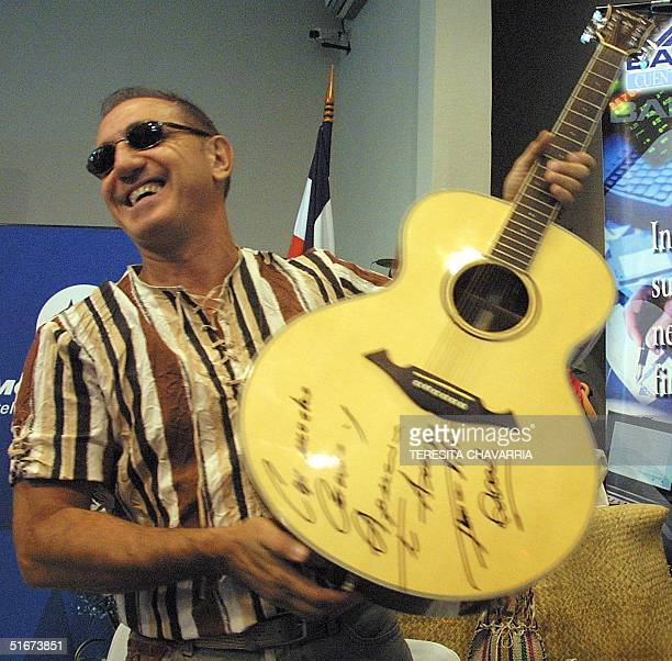 The Venezuelan musician Franco de Vita shows his autographed guitar during a press conference in San Jose Costa Rica 7 September 2002 As a part of...