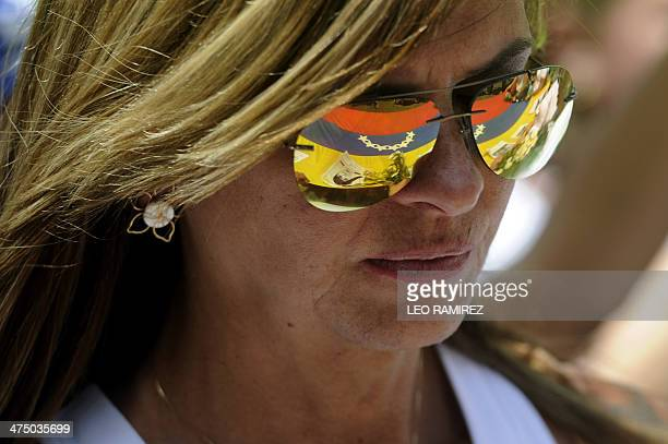 The Venezuelan national flag is reflected in a woman's sunglasses during a protest against the government of Venezuelan President Nicolas Maduro in...
