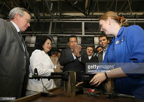 The Venezuelan President Hugo Chavez applauds a female worker who boresights an AK-103 assault rifle 26 July, 2006 during a visit to the Izhmash...