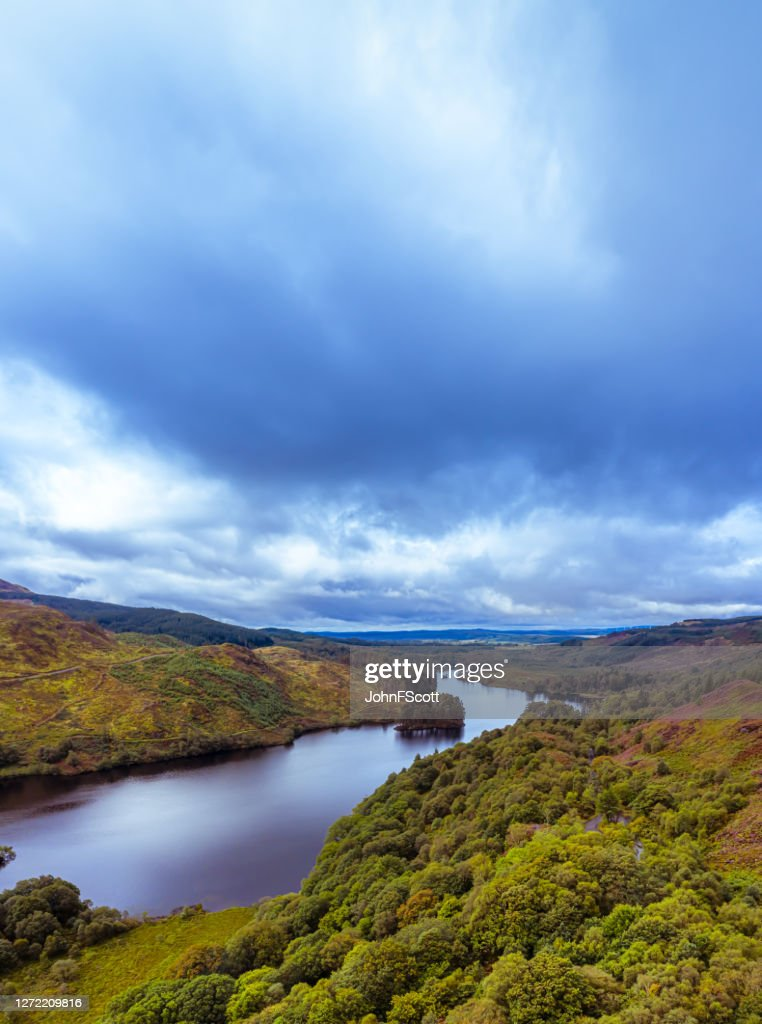 The vertical panoramic aerial view from a drone of a Scottish loch in Dumfries and Galloway on an overcast day : Stock Photo