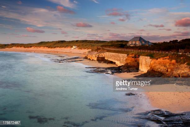 The very last rays of light illuminate the beach, dunes and walls of Constantine Bay.
