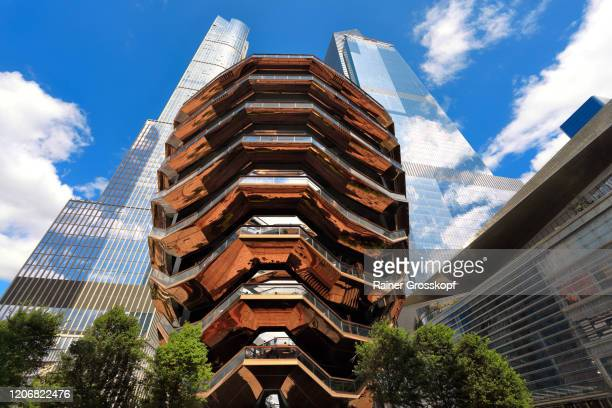 the vessel, a spirical staircase in front of skyscrapers against a cloudy sky - rainer grosskopf stock pictures, royalty-free photos & images