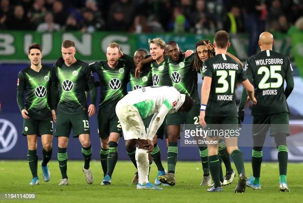 The VfL Wolfsburg team celebrate victory as Breel Embolo of Borussia Monchengladbach reacts to defeat after the Bundesliga match between VfL...