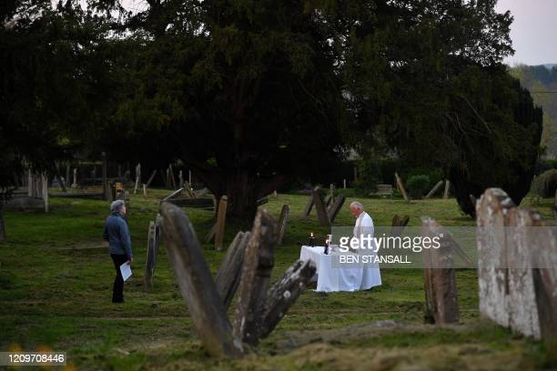 The Vicar of Brenchley Reverend Campbell Paget conducts an Easter Service to a single member of the congregation at dawn in the churchyard of All...