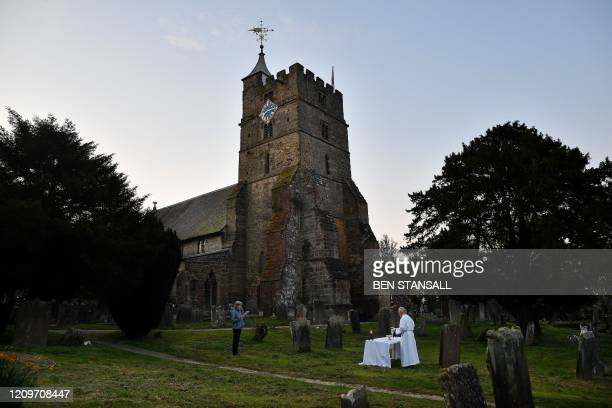 TOPSHOT The Vicar of Brenchley Reverend Campbell Paget conducts an Easter Service to a single member of the congregation at dawn in the churchyard of...