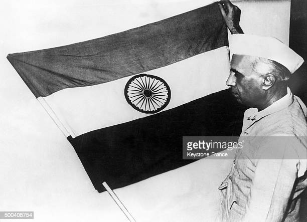 The vice President of India Jawaharlal Nehru presenting the national flag of India during a meeting of the constituent assembly the flag is made up...