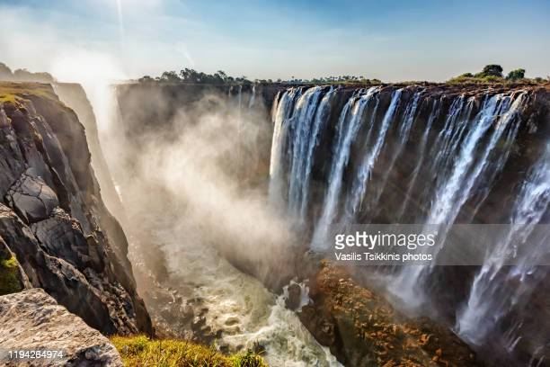 the victoria falls against the sun - victoria falls stock pictures, royalty-free photos & images