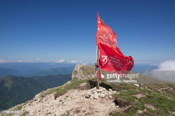 the victory banners on top of bolshoy tkhach, western caucasus - argenberg stock pictures, royalty-free photos & images