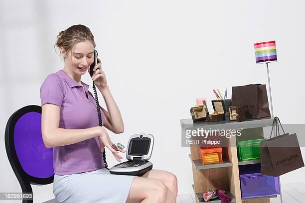 jeune femme montrant ses bagues Cocktail Ring de Louis VUITTON en téléphonant à son copain grâce au nouveau visiophone de France Telecom doté d'un...