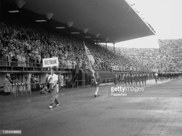 The Vietnamese flag bearer leading the Vietnam Olympic team at the opening ceremony of the 1952 Summer Olympics at the Helsinki Olympic Stadium in...