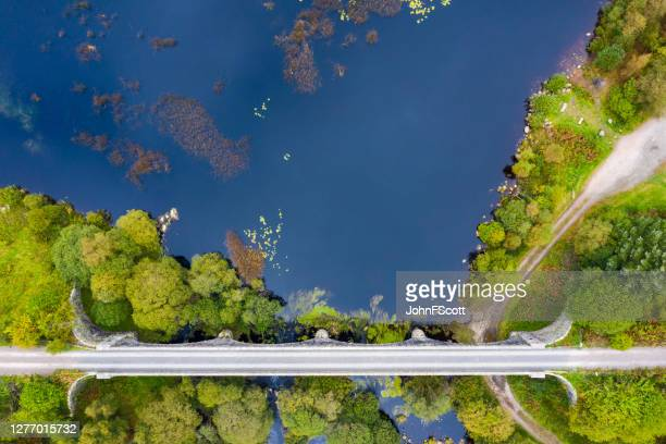 the view captured by a drone looking directly down on a disused railway viaduct in rural scotland - johnfscott stock pictures, royalty-free photos & images
