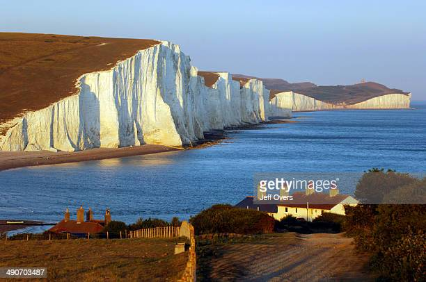The view east from Seaford Head East Sussex as evening sunshine illuminates the chalk cliffs of the Seven Sisters The seven peaks on the cliffs run...