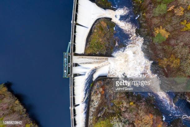 the view from a drone directly above water flowing over a hydro electric dam on an overcast day in dumfries and galloway south west scotland - flowing water stock pictures, royalty-free photos & images