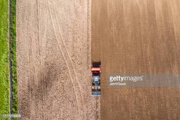 the view from a drone looking directly down on a tractor being used to pull a seed drill on a scottish farm on a late summer day - johnfscott stock pictures, royalty-free photos & images