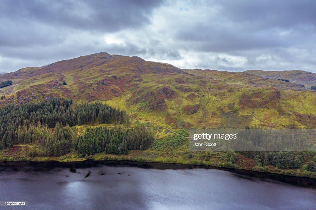 The view from a drone of a hill on the side of a Scottish loch in Dumfries and Galloway on an overcast day : Stock Photo