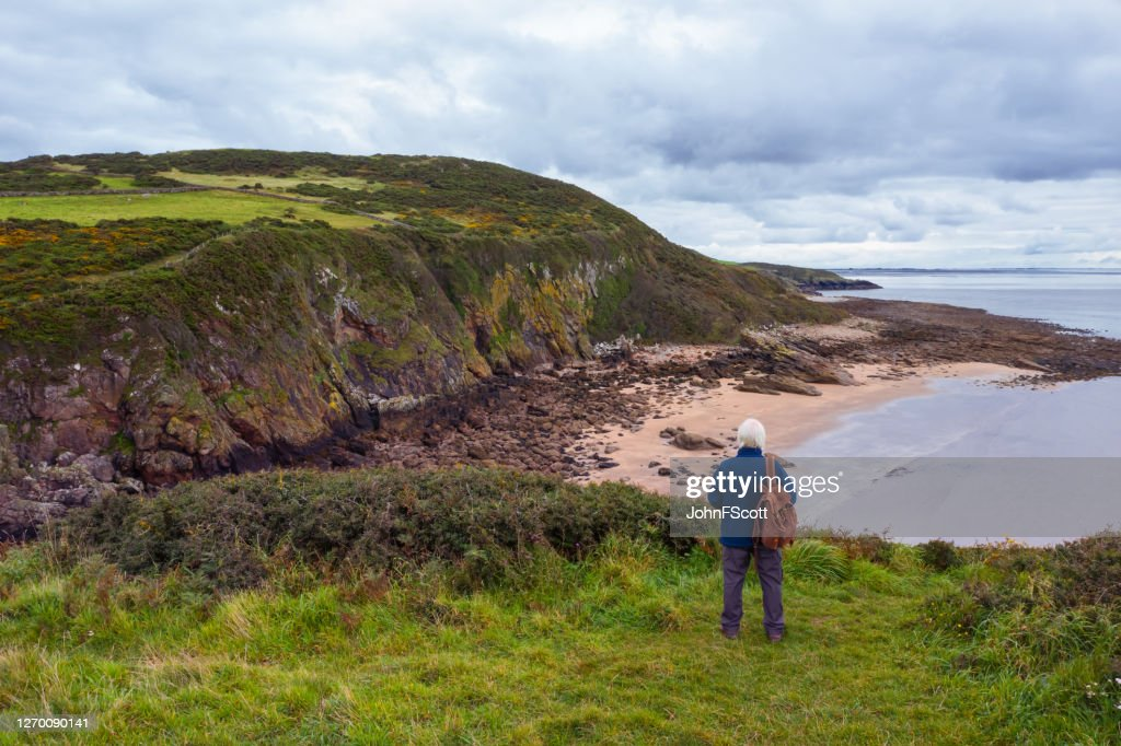 The view from a drone of a senior man standing alone at the coast in Dumfries and Galloway, south west Scotland : Stock Photo