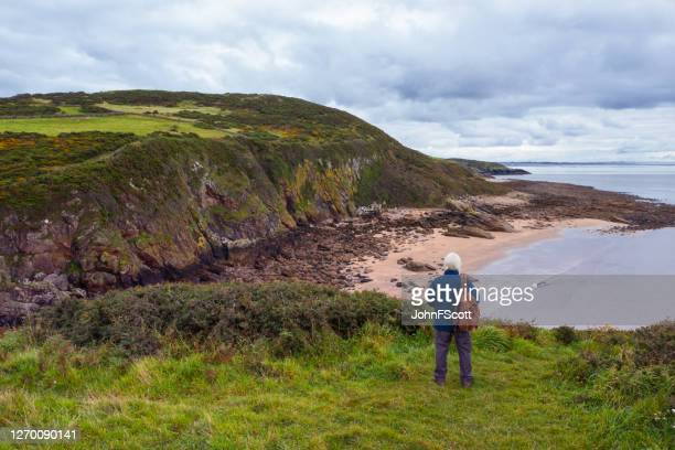 the view from a drone of a senior man standing alone at the coast in dumfries and galloway, south west scotland - johnfscott stock pictures, royalty-free photos & images