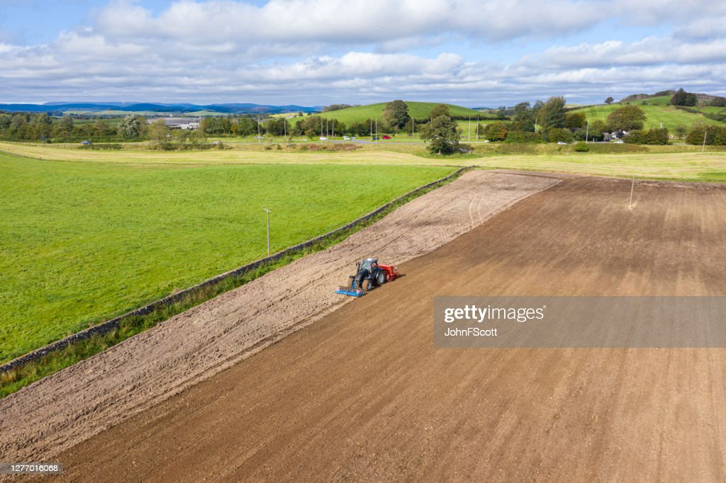 The view from a drone of a tractor being used to pull a seed drill on a Scottish farm on a late summer day : Stock Photo