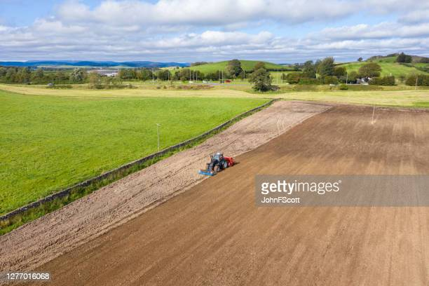 the view from a drone of a tractor being used to pull a seed drill on a scottish farm on a late summer day - johnfscott stock pictures, royalty-free photos & images