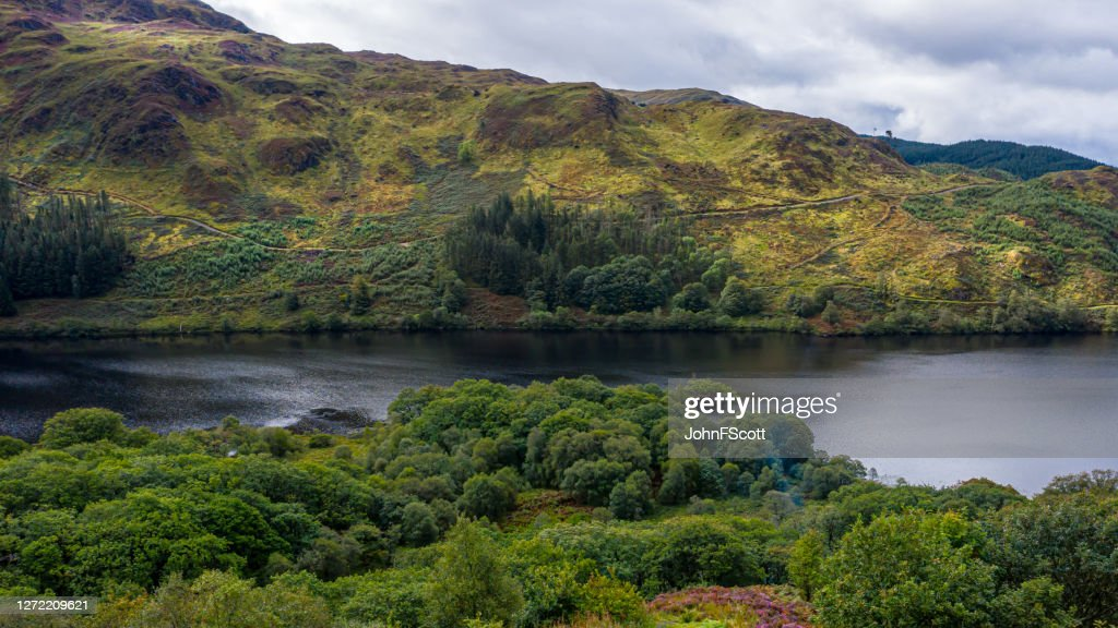The view from a drone of woodland and a loch in Dumfries and Galloway on an overcast day : Stock Photo