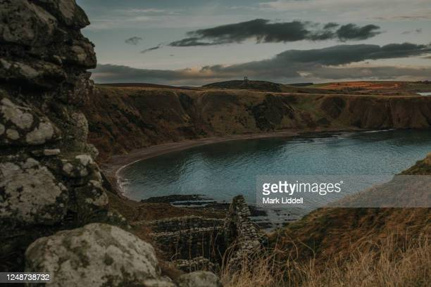 the view from dunnottar caste at sunset, looking out toward the stonehaven war memorial - dunnottar castle stock pictures, royalty-free photos & images