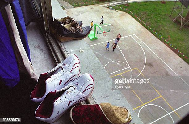 The view from Guo Jing and Wei Wen Qing's room looks out onto the factory basketball court Today some men from the factory are enjoying a game after...