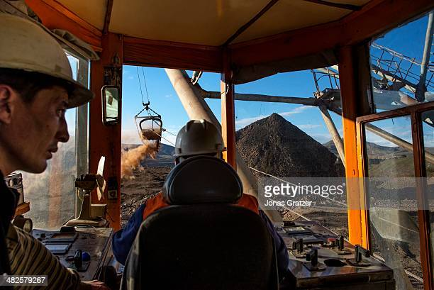 The view from inside an excavator where two men are digging up fossil fuels on the Sharyn Gol coal mine located in the Sharyngol district of...