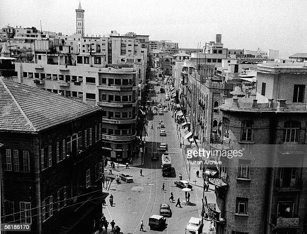The view looking down a street from above shows streetcars cars and pedestrians as they go about their daily business Beirut Lebanon early 1950s In...