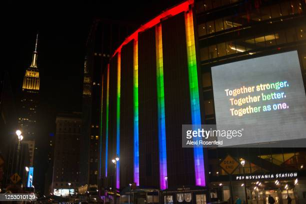 The view of Madison Square garden lit up in pride colors and a digital screen reads Together stronger Together better Together as one in rainbow...