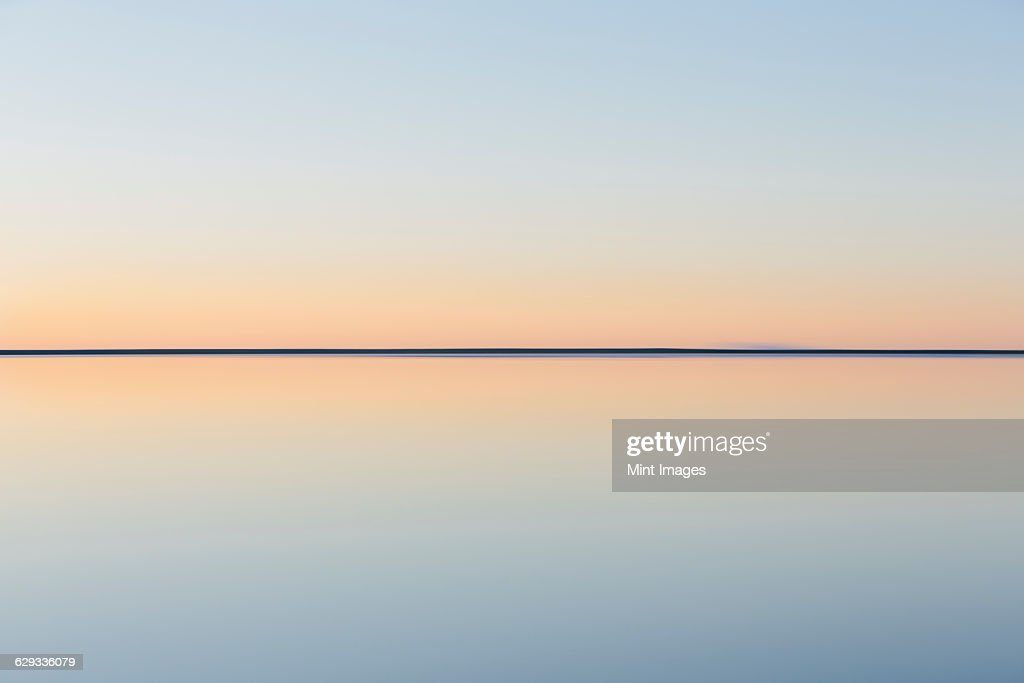 The view to the clear line of the horizon where land meets sky, across the flooded surface of Bonneville Salt Flats. Dawn light, : Stock Photo