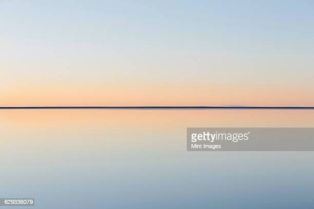 the view to the clear line of the horizon where land meets sky, across the flooded surface of bonneville salt flats. dawn light, - horizon over water stock pictures, royalty-free photos & images