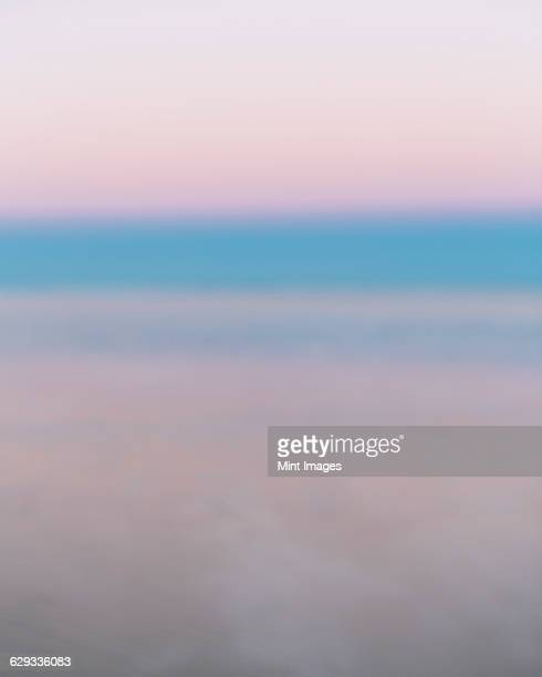 The view to the horizon across the flooded surface of Bonneville Salt Flats, at dawn or sunset. Pink and blue vivid colours.