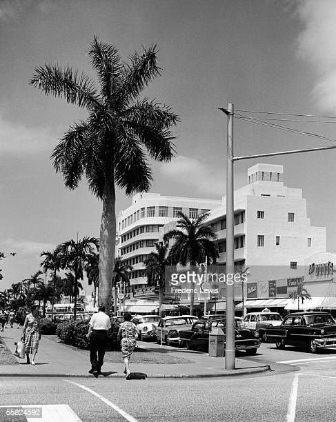 The view West along Lincoln Road at the intersection of Drexel Avenue, Miami Beach, Florida, late 1950s. Pedestrians walk along the side of the...