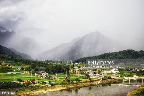 The village in mountains with rain mists