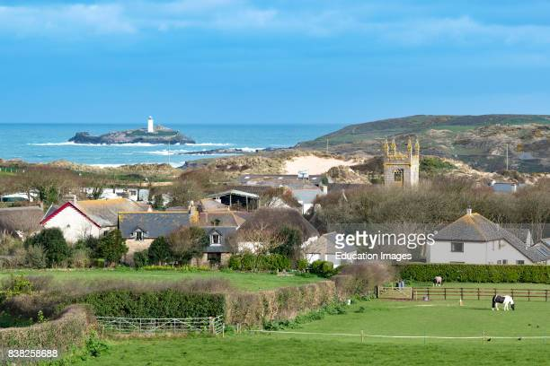 The village of Gwithian in Cornwall, England, UK Godrevy lighthouse is in the background.
