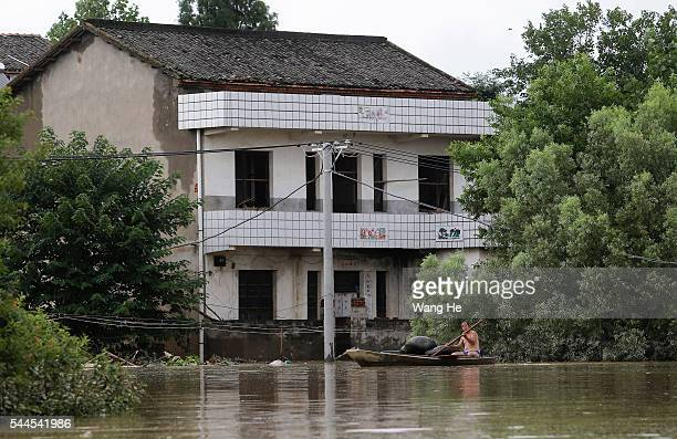 The villagers rowing in the flood after Jushui River broke the dyke and flooded XuJiaDun village in Wuhan in central China's Hubei province Saturday...