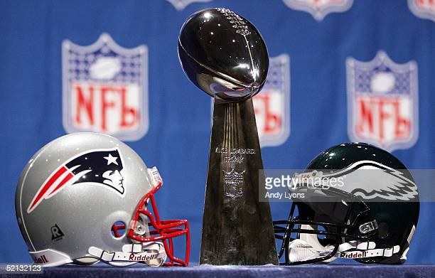 The Vince Lomabardi trophy which is to be awarded to the winner of the Super Bowl is pictured with the Patriots and Eagles helmets on February 4 2005...