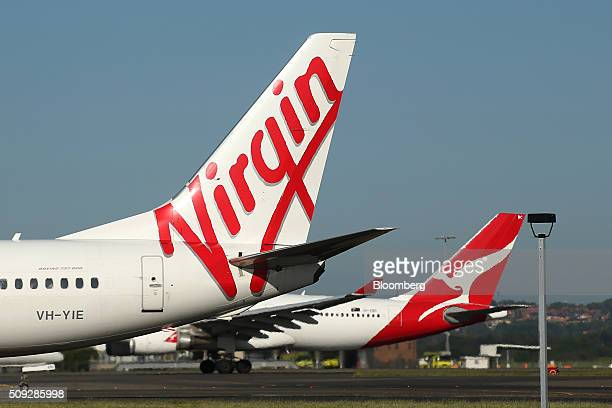 The Virgin Australia Holdings Ltd logo left and Qantas Airways Ltd logo are displayed on the tails of aircraft at Sydney Airport in Sydney Australia...